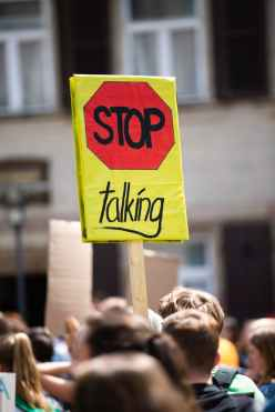 selective photo of stop talking sign carried by people walking on street